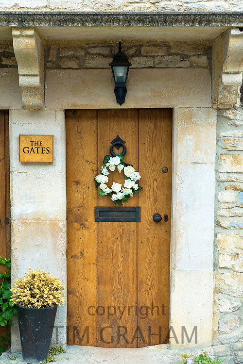 Traditional English oak timber front door of country cottage with flower garland in quaint village of Castle Combe in The Cotswolds, UK