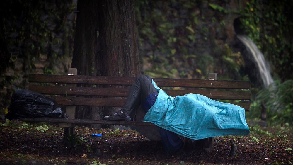 A homeless man lays on a bench on Historic River Street , Monday, Sept., 11, 2017, in Savannah, Ga., as Hurricane Irma starts to impact the area. (AP Photo/Stephen B. Morton)