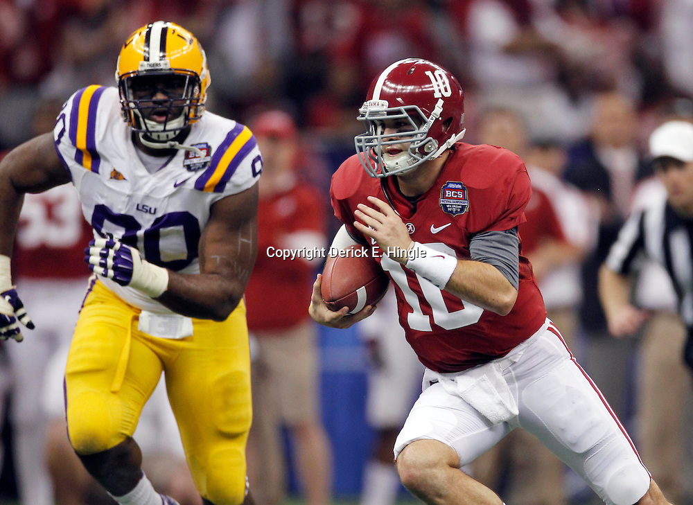 Jan 9, 2012; New Orleans, LA, USA; Alabama Crimson Tide quarterback A.J. McCarron (10) runs past LSU Tigers defensive tackle Michael Brockers (90) during the first half of the 2012 BCS National Championship game at the Mercedes-Benz Superdome.  Mandatory Credit: Derick E. Hingle-US PRESSWIRE