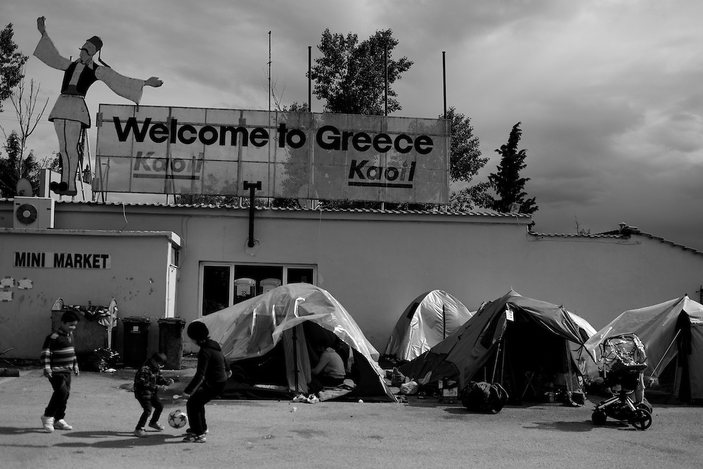 "Refugee children are playing near a neon sign reads ""Welcome to Greece!"", at the Hotel Hara, a roadside bungalow in the village of Evzoni, seven kilometers south of the Greek Macedonian border. The gas station and surroundings of Hotel Hara have become a makeshift refugee camp."