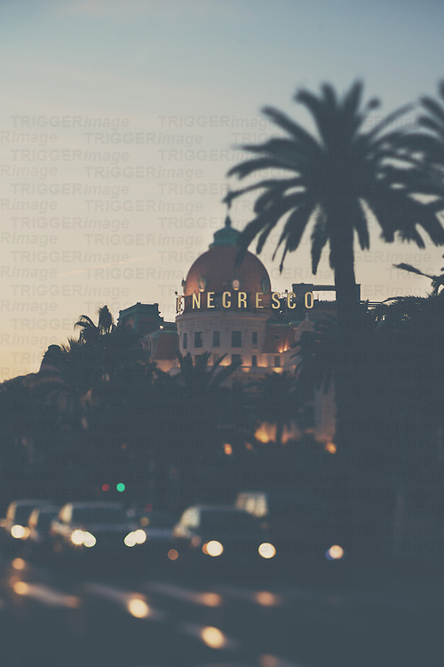 The hotel negresco at sunset with cars driving along in front of it