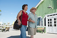 Senior couple on vacations, walking arm in arm