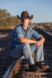 cowboy sitting on railroad tracks