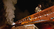 A Decatur firefighter makes his way down an aerial ladder as he helps battle a blaze in the Cardinal Apartments in Decatur. Photo/Gary Cosby Jr.