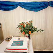 A 40th anniversary celebration cake has been baked for the elite 'Red Arrows', Britain's prestigious Royal Air Force aerobatic team who are soon to appear. Displayed in a hospitality tent at the Kemble Air Show, the iced gateau has a red ribbon and an image of nine aircraft in mid-flight. A bouquet of flowers and assorted cutlery for the forthcoming lunch is alongside. Blue paper is draped over the top adding to the patriotic red, white and blue colours. After several identities, the Red Arrows started life near this location in 1964 at RAF Little Rissington in Gloucesterhire. Their name originates from the French 'Fleches Noirs', or Black Arrows, so in England, a new team was established flying black Hawker Hunters in the colour of their Squadron 111. As the Red Arrows diaplay team, they have since flown over 4,000 shows in 52 countries.