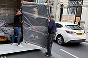 Art removal specialist workmen offload an artwork by the photographer Romina Ressia from the back of their van in Maddox Street, on 30th April 2019, in London, England