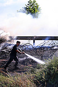 Fire fighter fighting the flames of a bush fire