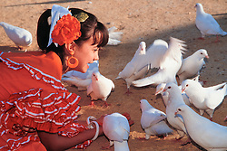 Europe, Spain, Sevilla (also known as Seville), girl in flamenco dress feeding doves during annual Feria de Abril festival