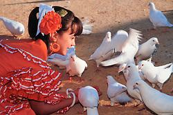 Europe, Spain, Sevilla (also known as Seville), girl in flamenco dress feeding doves during annual Feria de Abril festival