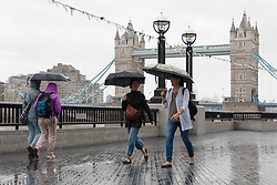 © Licensed to London News Pictures. 29/07/2018. London, UK.  Tourists are caught in a heavy rain shower in central London near Tower Bridge this morning.  Photo credit: Vickie Flores/LNP