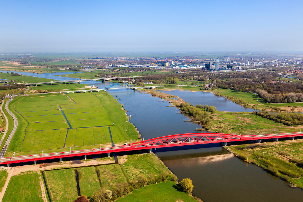 Nederland, Gelderland - Overijssel, Hattem, 01-05-2013; IJsselbrug, spoorbrug bij Hattem voor de Hanzelijn. In de achtergrond de brug voor regionaalautoverkeer en de brug in rijksweg A28 naar Zwolle. <br /> De 'Hanzeboog' is ontworpen door  Quist Wintermans Architecten.<br /> Bridges over the river IJssel near Zwolle. The red railway bridge Hanzeboog (Hanseatic arch) over the IJssel near Zwolle, has been designed by Quist Wintermans Architects.  <br /> luchtfoto (toeslag op standard tarieven);<br /> aerial photo (additional fee required);<br /> copyright foto/photo Siebe Swart