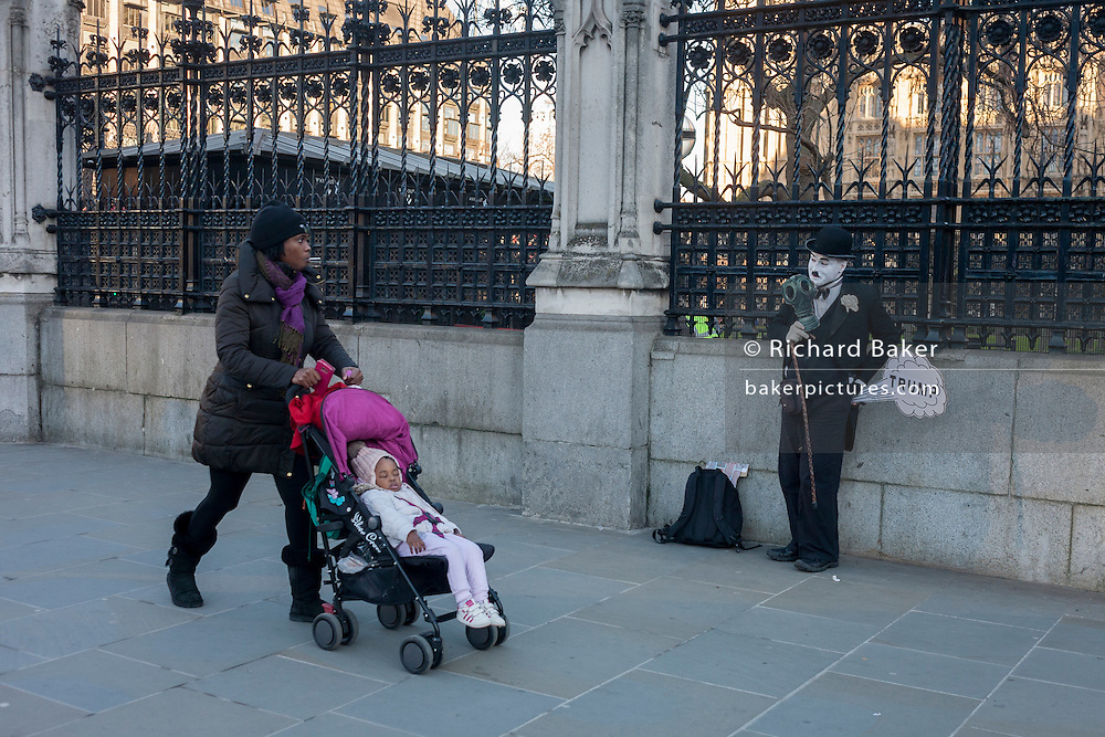 Outside Britain's Palace of Westminster parliament, a black mother walks past a Charlie Chaplin character making a Donald trump joke, on the day of Trump's inauguration as the 45th US president, on 20th January, in Parliament Square, London borough of Westminster, England.