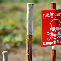 Cambodia has been dealing with the insurmountable task leftover from decades of war and its legacy, unexploded ordnance or UXOs. Estimates range from 3 to 9 million unexploded bombs that are still just beneath the surface throughout the region. These bombs are left over from air strikes, artillery fire, mortar shells, rockets, grenades, anti-personnel and anti-vehicle land mines are indiscriminate weapons and do not expire, often killing or injuring between 100 to 200 people in Cambodia a year. With little resource, the countries' people and Non Governmental Organizations (NGOs) are still facing over a hundred years being exposed to this deadly issue while walking and cultivating their land in fear.<br /> <br /> A sign posted in an uncleared field in the Cambodian countryside province of Kampong Thom marks the danger of un-exploded bombs,  Jan. 2013.