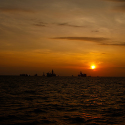 The Transocean Development Driller III and Transocean Development Driller II along with vessels leased by BP Plc are seen silhouetted during sunrise at the BP Plc Macondo well site in the Gulf of Mexico off the coast of Louisiana, U.S., on Friday, July 30, 2010. BP Plc continues to work on a relief well to permanently plug the source of the largest oil spill in U.S. history.  Photographer: Derick E. Hingle/Bloomberg