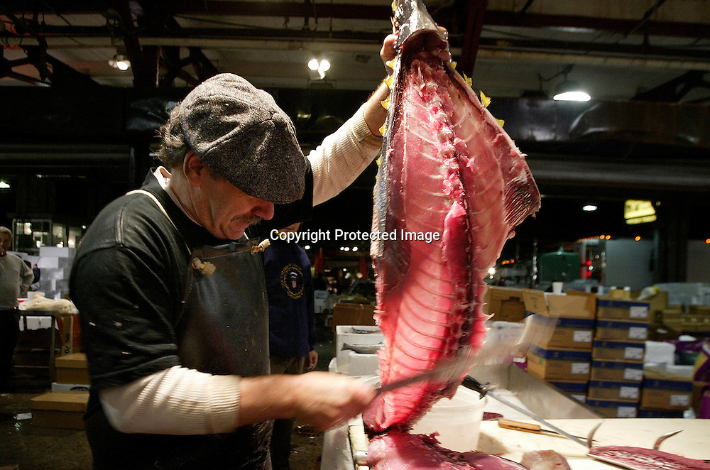 Bobby DiGregorio filkets a tuna at the Fulton Fish Market in New York November 10, 2005. After more than 170 years of operation, the Fulton Fish Market is scheduled to move to a new indoor facility the Bronx by week's end.