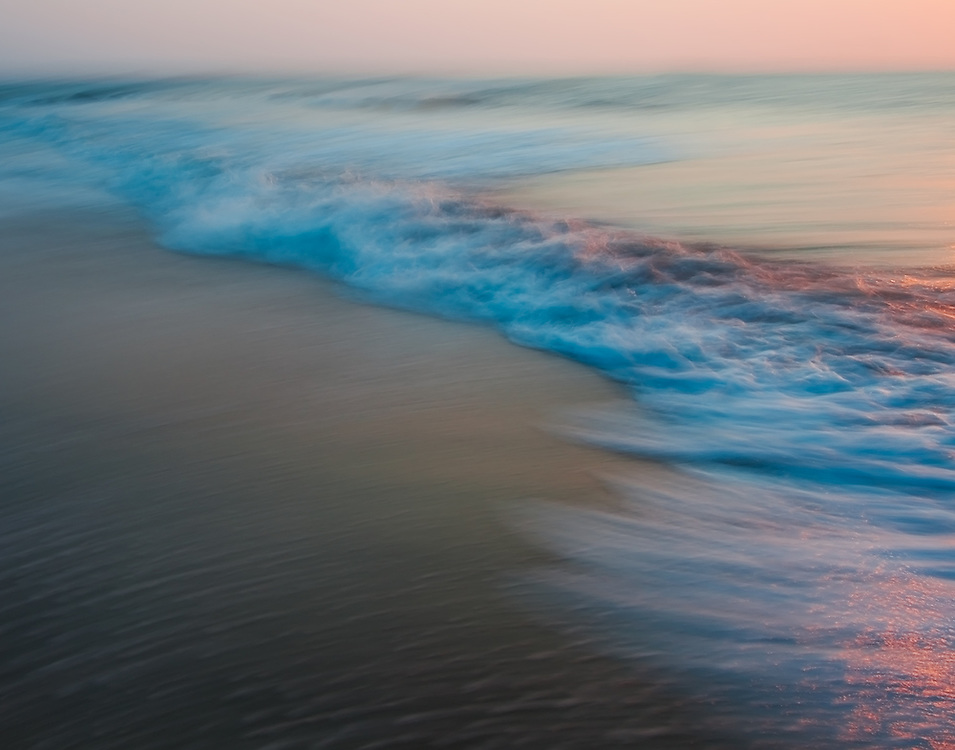 Waves crash onto shore at Tybee Beach at sunrise. Using the pastels from the early morning light, long exposures, and precise camera panning , I was able to create this waterscape abstract.