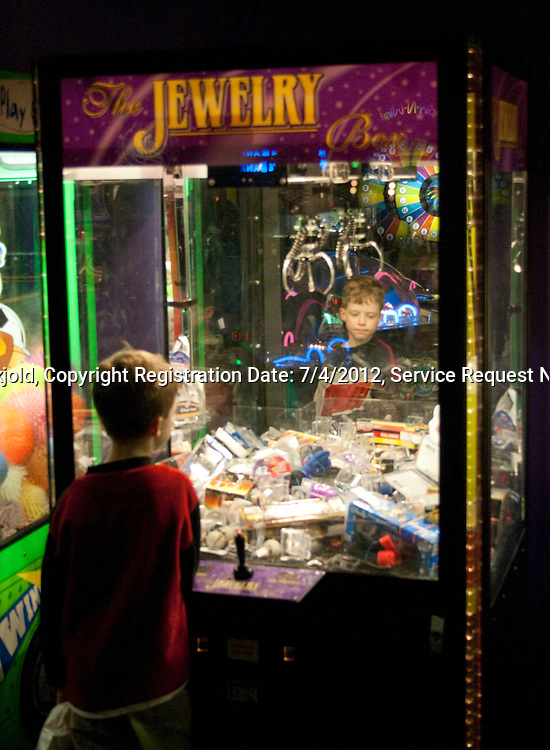 Boy age 8 playing the Jewelry Box crane machine arcade claw game. Grand Slam Amusement Center Burnsville Minnesota MN USA