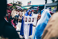A woman holds up likenesses of Jesus Christ during the Holy Week festival in Pampanga, the Philippines.