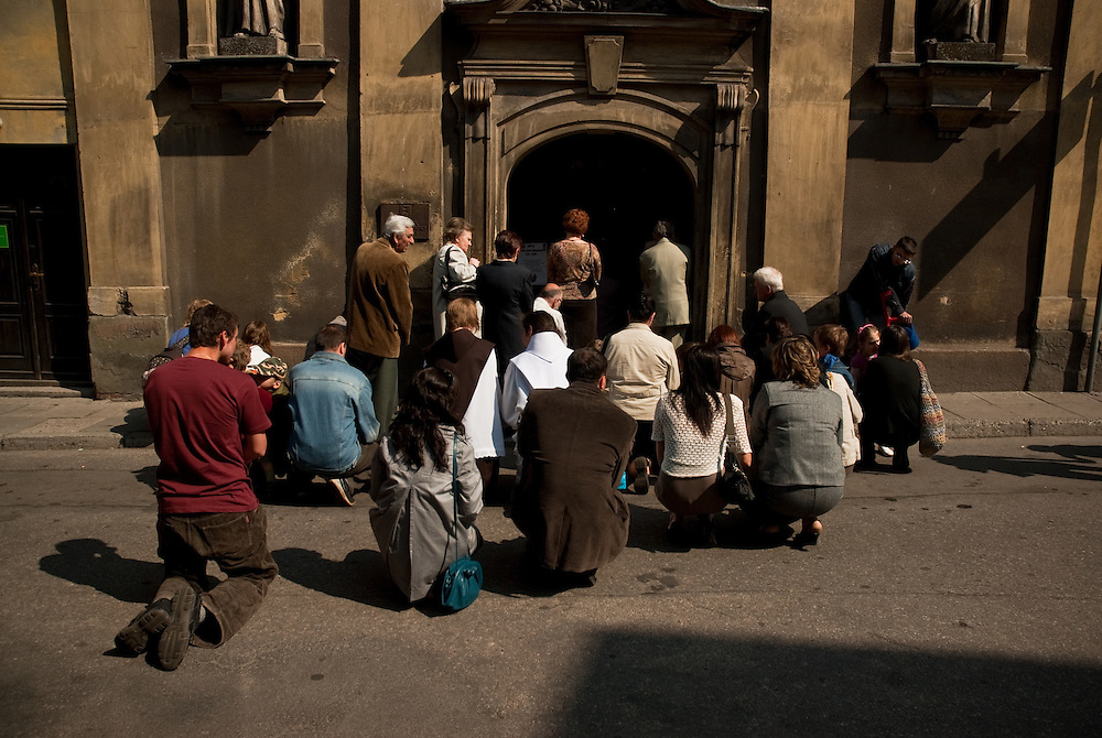 Church goers praying on the street outside a full church in Cieszyn, Silesia, Poland. April 2009.