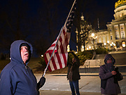 17 DECEMBER 2019 - DES MOINES, IOWA: A man carries an American flag in front of the Iowa State Capitol during a protest in support of the impeachment of President Donald Trump. About 300 people came to the Iowa State Capitol in Des Moines in near freezing weather to call for the impeachment of President Donald Trump. The rally, and others like it around the US, come on the eve of an impeachment vote in the US House of Representatives.          PHOTO BY JACK KURTZ