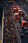 Seen from an office block high vantage point, thousands of commuters pour northwards over London Bridge against the direction of queueing buses and cars. It is a scene about the transient business community and mass transport. The working population arrives early for work over the bridge in the City of London's historic financial district. We see the sunlit faces of those walking towards the viewer which echo the red tail lights of the stationary vehicles. So gridlocked is the traffic on the southbound carriageway, there is a lone cyclist stuck and squeezed between the curb and a double-decker bus. On the other side of the road, the street is almost empty of motors adding to the drama and chaos. The City of London has a resident population of under 10,000 but a daily working population of 311,000. The City of London is a geographically-small City within Greater London, England. The City as it is known, is the historic core of London from which, along with Westminster, the modern conurbation grew. The City's boundaries have remained constant since the Middle Ages but  it is now only a tiny part of Greater London. The City of London is a major financial centre, often referred to as just the City or as the Square Mile, as it is approximately one square mile (2.6 km) in area. London Bridge's history stretches back to the first crossing over Roman Londinium, close to this site and subsequent wooden and stone bridges have helped modern London become a financial success. ...