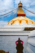 A woman prays at Boudhanath stupa