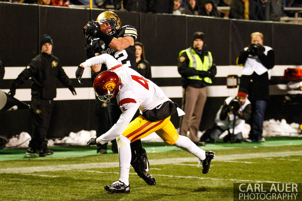 November 23rd, 2013:  Colorado Buffaloes sophomore wide receiver Nelson Spruce (22) pins the ball to his face to hold on for a touchdown past the defense of USC Trojans senior corner back Torin Harris (4) in the fourth quarter of the NCAA Football game between the University of Southern California Trojans and the University of Colorado Buffaloes at Folsom Field in Boulder, Colorado