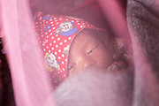 Sapana Baniya (now 2 months) lies in his cradle in their temporary home in Chautara, Sindhupalchowk, Nepal on 29 June 2015. Sapana was only days old when she lost her mother during the April 25th earthquake that completely levelled their house. Her sister Aastha was buried under the rubble together with her mother but Aastha survived. As their father Ratna Baniya (28) cannot care for the children on his own, SOS Childrens Villages has since been supporting the grandmother with financial and social support so that she can manage to raise the children comfortably and ensure that they will all be schooled. Photo by Suzanne Lee for SOS Children's Villages