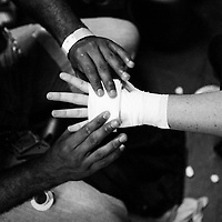 Jae McIntosh, left, wraps up the hand of Keelee McCarty before her MMA fight on Saturday, August 5th during the Summit Fighting Championships match at the Tupelo Furniture Market.