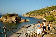 Spanien Spain,Mallorca Balearen..Alcudia..Bucht von Pollenca, Kueste, kleine Insel, Strand, Maedchen gehen zum strand..Pollenca Bay, beach, girls going to the beach....