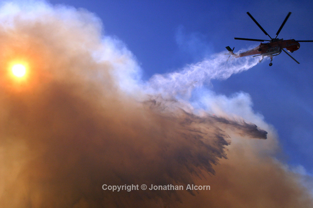 Oct 21, 2007 Malibu, CA, USA - A firefighting Sikorski helicopter makes a water drop on a wind whipped wildfire near Carbon Canyon on Sunday , October 21, 2007 in Malibu , California. .