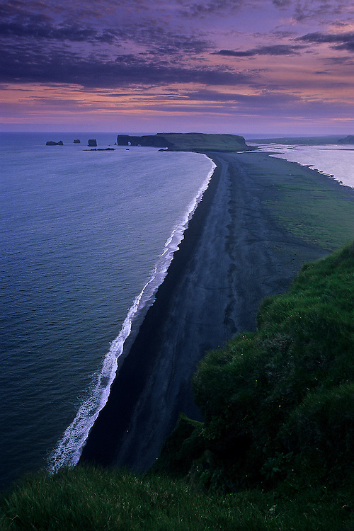 The black sand beach of Reynisfjara, near Vik, in southern Iceland, leads to the promontory of Dyrholaey in the background