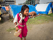 05 AUGUST 2015 - KATHMANDU, NEPAL: A girl washes her face in a large Internal Displaced Person (IDP) Camp in the center of Kathmandu. The camp is next to one the most expensive international hotels in Kathmandu. More than 7,100 people displaced by the Nepal earthquake in April live in 1,800 tents spread across the space of three football fields. There is no electricity in the camp. International NGOs provide water and dug latrines on the edge of the camp but the domestic waste water, from people doing laundry or dishes, runs between the tents. Most of the ground in the camp is muddy from the running water and frequent rain. Most of the camp's residents come from the mountains in northern Nepal, 8 - 12 hours from Kathmandu. The residents don't get rations or food assistance so every day many of them walk the streets of Kathmandu looking for day work.      PHOTO BY JACK KURTZ