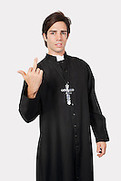 Portrait of young man in priest costume with rude gesture against gray background