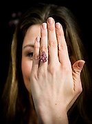 UNITED KINGDOM, London:  A woman poses wearing a vivid pink pear-shaped 15.38 carat diamond called the 'Unique Pink' at a press preview at Sotheby's in London, on April 7, 2016. The diamond is expected to sell for £19-26 million pounds at auction in Geneva. Pic by Andrew Cowie / Story Picture Agency