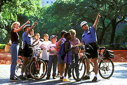Stock photo of bicycle patrol officers showing points of interest to a group of children