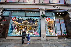© Licensed to London News Pictures. 23/12/2019. Mother and son look in Hamleys shop window in Regents Street which is normally packed with traffic remains empty as shops in the West End prepare for last minute Christmas shoppers. Alex Lentati/LNP