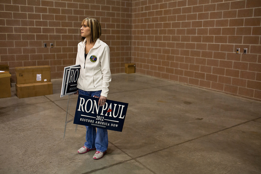 A woman holds yard signs after Republican presidential candidate Ron Paul spoke at a Salute to Veterans Rally on Wednesday, December 28, 2011 in Des Moines, IA.