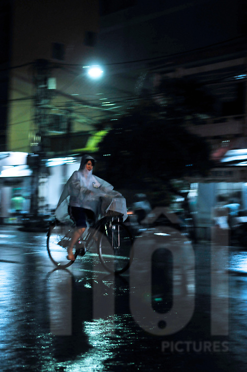 A young Vietnamese woman rides a bicycle at night during monsoon season. Nha Trang, Vietnam, Southeast Asia