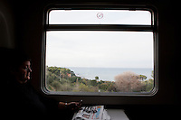 A passenger looks at the Sicilian landscape from the window on the last Trinacria train. The Trinacria express train is a historical train from Palermo, Sicily, to Milan, symbol of the emigration from South to the North.  From December 11th 2011 16 train connecting Southern Italy to the North will be cancelled by Trenitalia, the state-owned train operator in Italy. ### Un passeggero osserva il paesaggio dal finestrino dell'ultimo treno Trinacria. Il Trinacria è un treno storico che ha collegato Palermo e Milano, simbolo dell'emigrazione verso Nord. Dall'11 dicembre 2011 16 treni che collegano il Sud al Nord Italia verranno soppressi da Trenitalia.