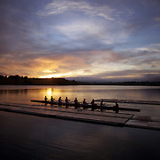 An eight crew prepare to row during a beautiful sunrise on Lake Karapiro, near Cambridge, Waikato. Many national and international rowing competitions are held on Lake Karapiro which is also the home of The Rowing New Zealand High Performance Centre. Lake Karapiro hosted the 2010 World Rowing Championships. Lake Karapiro, Waikato,  New Zealand. 15th December 2010. Photo Tim Clayton
