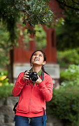 Jenny Kimura '17, photographs a spider web on lower campus between Rieke and Mary Baker Russell at PLU on Tuesday, Oct. 7, 2014. (PLU Photo/John Froschauer)