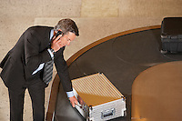 Business man claiming suitcase at luggage carousel in airport