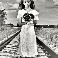 Female youth outdoors holding sunflowers standing on train track in summer