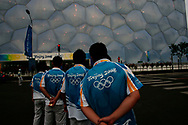 Olympic volunteers patiently wait to aid someone outside the Water Cube at the Olympic green in Beijing , China, Wednesday, Aug.20, 2008. It is one of the strangest things about the Olympics: From far away, it looks very close.Watching the Olympics on television, the athletes are right in front of you.  Up close, though, it's normally a different story. From the spectators' stands, the athletes are often just distant specks amid the enormity of some of the largest sports stadiums in the world. And there's so much else to grab your attention. There are snack bars,Coke machines, and life-sized cutouts of Chinese athletes with which you can pose. There are parades of Fuwas, the Olympic mascots. There are dancing fountains in front of the Water Cube, and thousands of volunteers to help you out. (Elizabeth Dalziel)