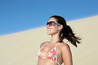beautiful smiling bikini dressed young brazilian  woman in the wind of the sand dune of jericoacoara ceara state near fortaleza looking at the sun