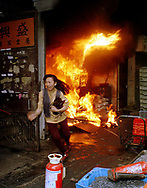 A woman escapes from a fire in a factory in Hunghom, Hong Kong.