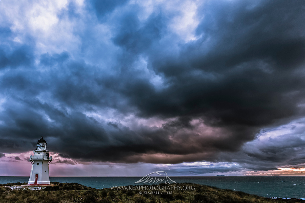 A southwesterly storm rapidly approaches the Waipapa Point Lighthouse at sunset, in the Catlins, New Zealand.