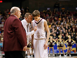 Wheeling Central Assistant Coach talks explains to Wheeling Central guard Owen Gainer (12) the next play call during a semi final round game at the Charleston Civic Center.