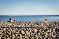 ACCIAROLI (POLLICA), ITALY - 5 OCTOBER 2016: 76-years-old Enzo Speranza (right) watches a toddler and his mother on the beach of Acciaroli, a hamlet in the municipality of Pollica, Italy, on October 5th 2016. Mr Speranza, who lives in Vallo della Lucania (about 30 kilometers from Acciaroli) spends 3 months a year in Acciaroli because of its fresh air and healthy lifestyle. He comes to the beach to exercise and relax every day.<br /> <br /> To understand how people can live longer throughout the world, researchers at University of California, San Diego School of Medicine have teamed up with colleagues at University of Rome La Sapienza to study a group of 300 citizens, all over 100 years old, living in Acciaroli (Pollica), a remote Italian village nestled between the ocean and mountains in Cilento, southern Italy.<br /> <br /> About 1-in-60 of the area's inhabitants are older than 90, according to the researchers. Such a concentration rivals that of other so-called blue zones, like Sardinia and Okinawa, which have unusually large percentages of very old people. In the 2010 census, about 1-in-163 Americans were 90 or older.